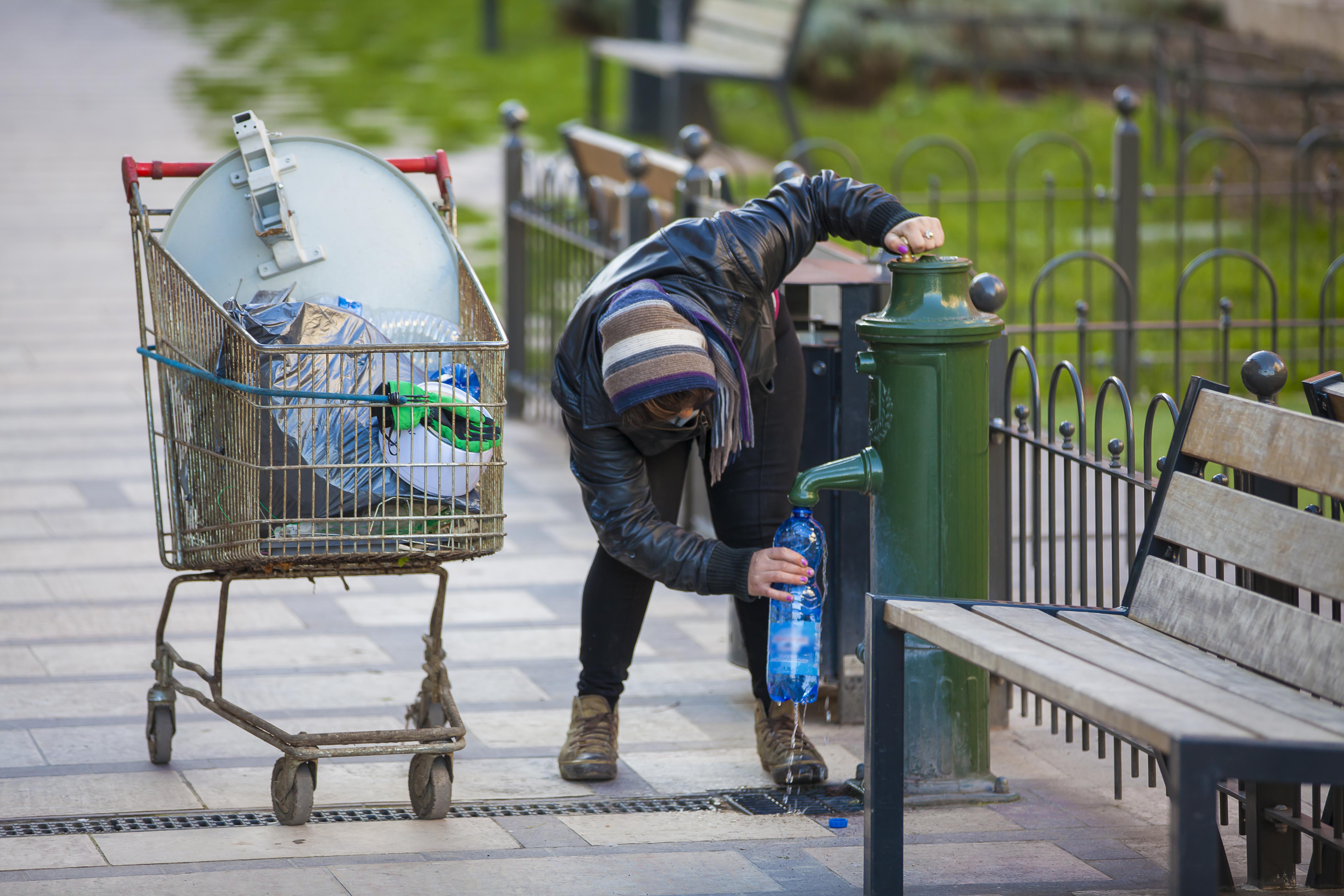 Personne sans-abri remplissant de l'eau à une fontaine public