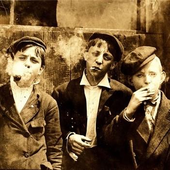 Photo d'époque représentant 3 jeunes garçons fumant cigarettes et pipes