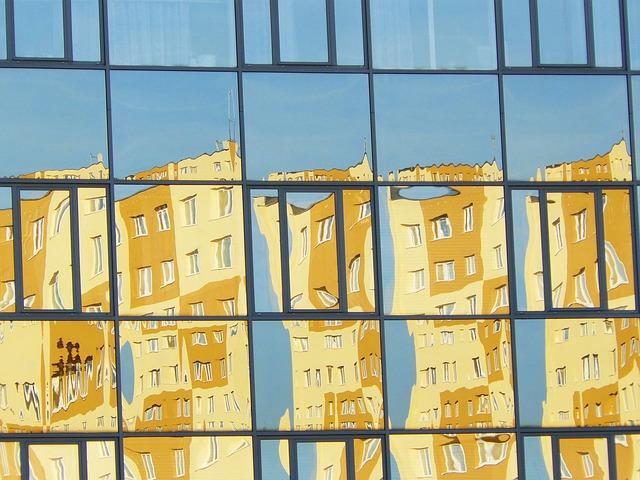 Photographie d'une paroi vitrée réfléchissant une immeuble jaune