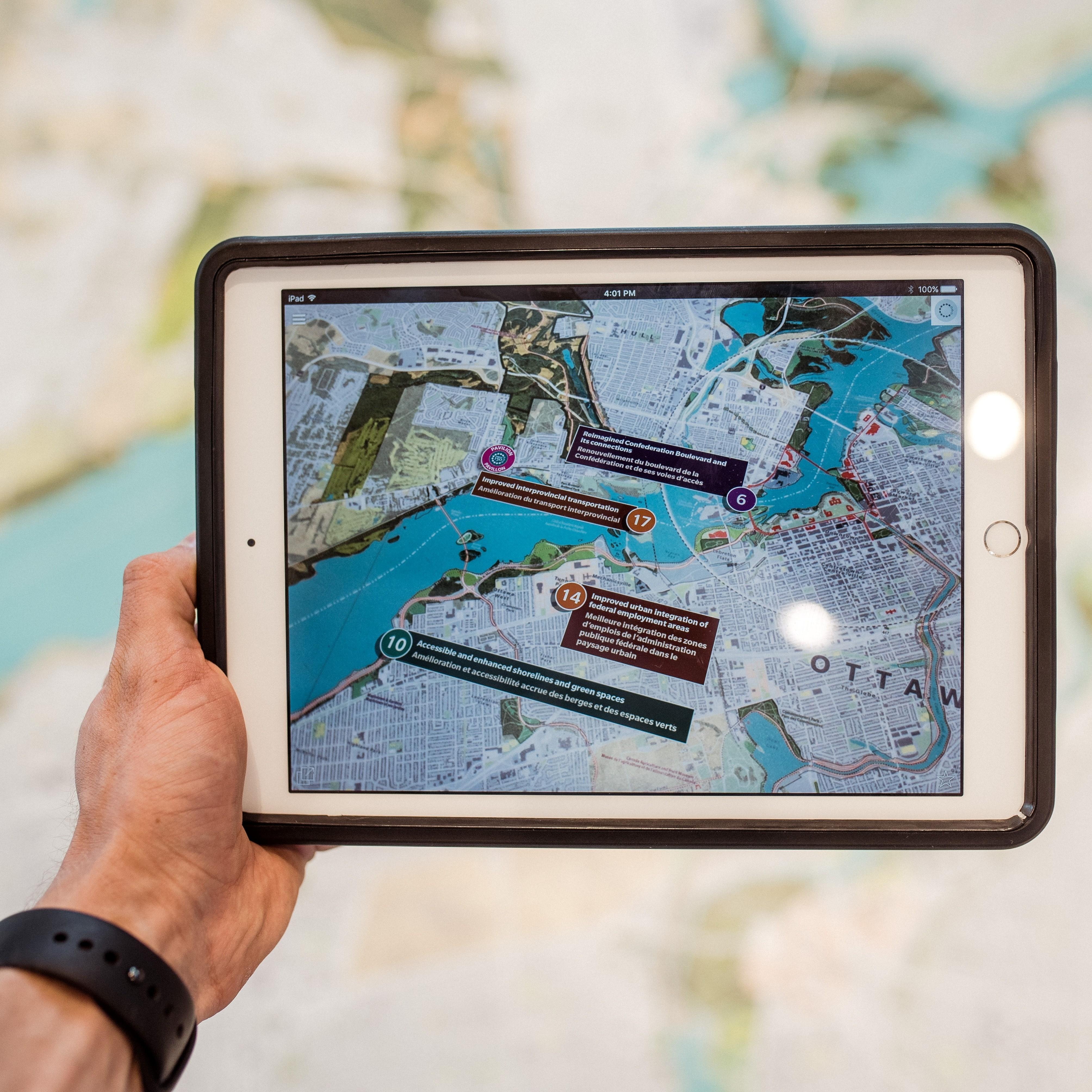 Photographie d'un personne utilisant un plan sur tablette pour observer le territoire sur lequel il se situ