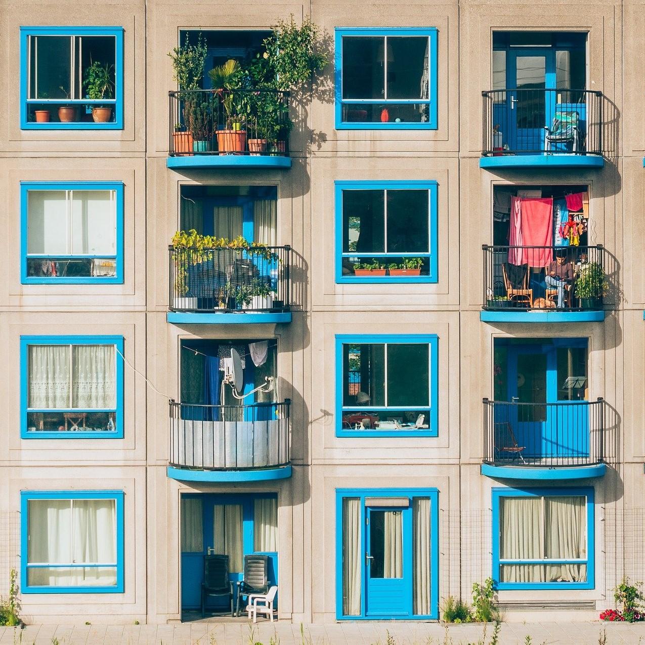 Photographie d'une façade d'immeuble aux encadrements de fenêtres bleus