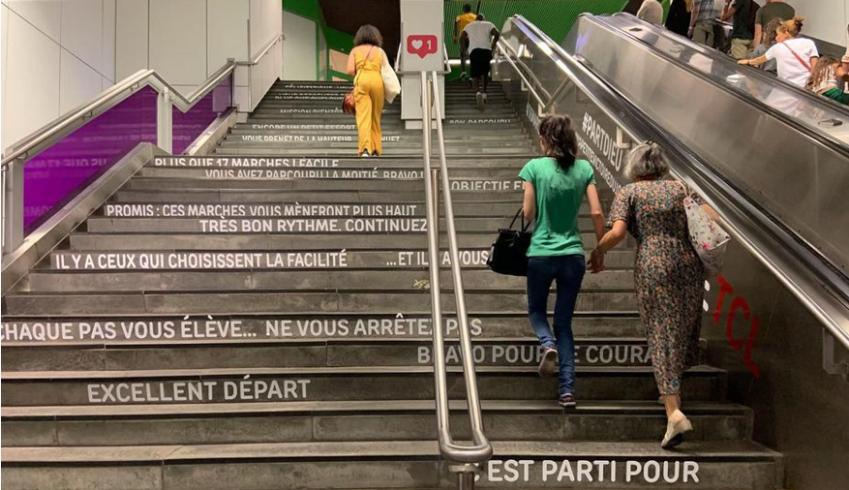 """Photographie de marches d'escalier où des stickers indiquent """"Vous avez parcouru la moitié bravo !"""" ; """"Promis : ces marches vous mèneront plus haut"""" ; """"très bon rythme. Continuez"""" ; """"Il y a ceux qui choisissent la facilité ...Et il y a vous"""" ; Chaque pas vous élève... Ne vous arrêtez pas"""" ; """"Excellent départ"""""""
